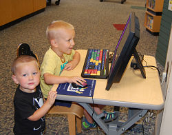 Jeremy James and Lazarus Romig play educational games on the new AWE Early Literacy Station.